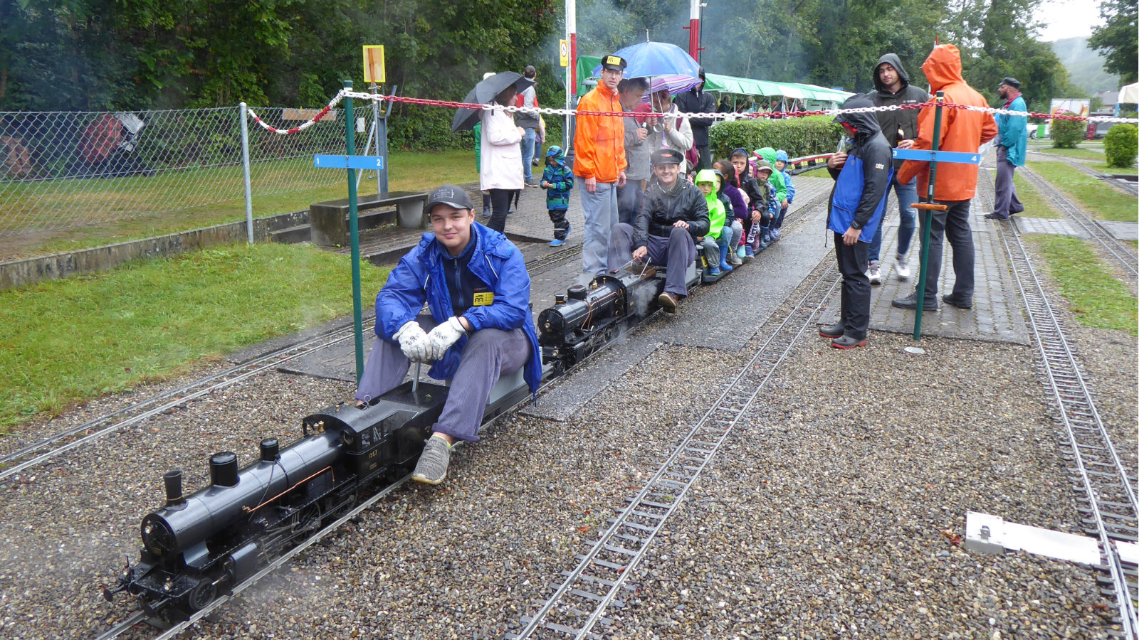 trotz Dauerregen ein Lächeln im Gesicht: Lokomotivführer der Dampflokomotiven